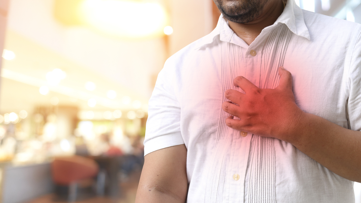 Man in shirt experiencing a sharp pain in his chest