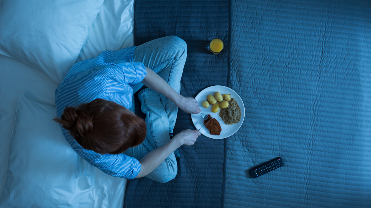 Woman who eats at night on her bed