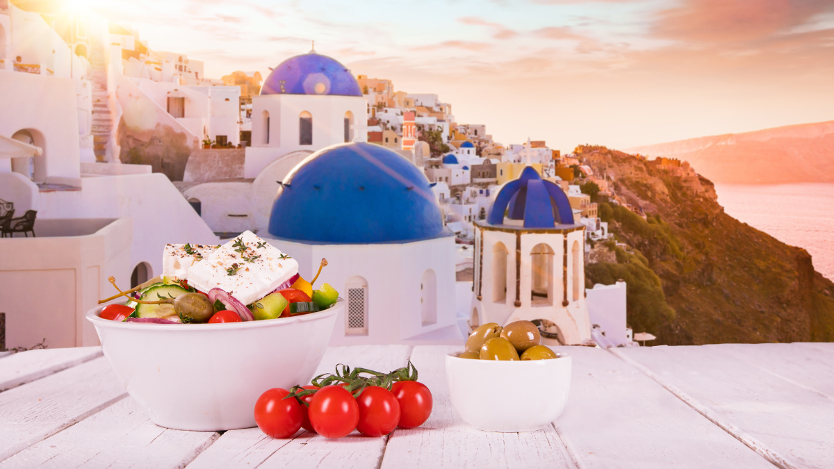 Mediterranean diet with tomatoes and olives, with the Greek landscape in the background